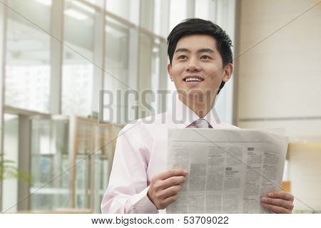 Young businessman in pink button down shirt reading newspaper