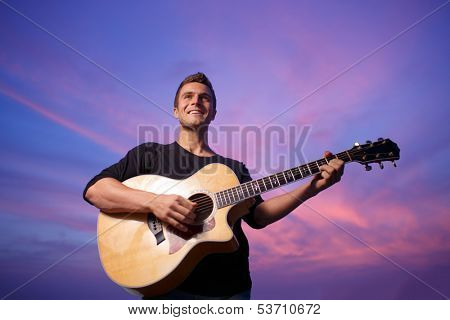 Young man playing guitar over sunset sky background