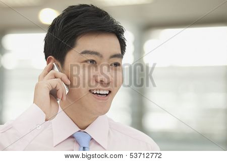 Young businessman in pink button down shirt on the phone