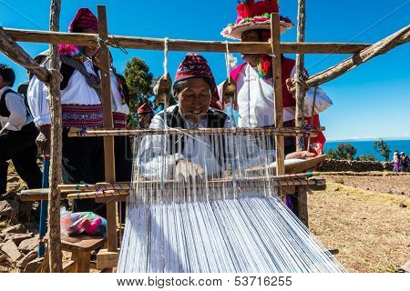 PUNO, PERU - JULY 25: men weaving in the peruvian Andes at Taquile Island on Puno Peru at july 25th, 2013. The highest point of the island is 4050 masl and the main village is at 3950m