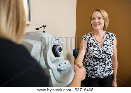Happy mature optician and patient shaking hands in clinic