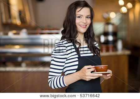 Portrait of beautiful waitress holding coffee cup while standing in cafeteria