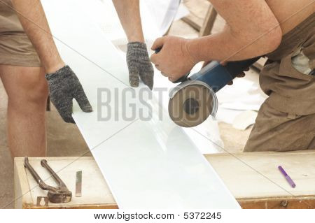 Construction Activity: Two Workers Sawing  Plastic Panel