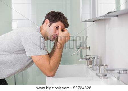 Side view of a tensed young man at washbasin in bathroom