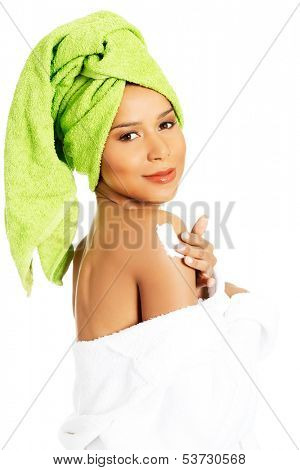Attractive woman rubbing a body lotion on her arm. Side view. Wrapped in towel with turban. Isolated on white.