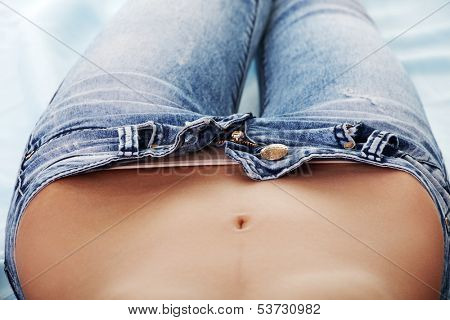 Woman's belly, open jeans. Up front view.Isolated on white.