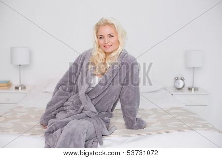 Portrait of a smiling casual young woman in bathrobe sitting on bed at home
