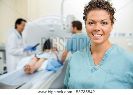 Portrait of happy female nurse with colleague and doctor preparing patient for CT scan in hospital