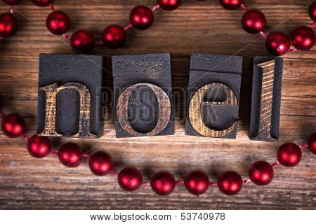 The word NOEL written with vintage wood printer blocks. Christmas message over old wood with a string of decorative red beads.