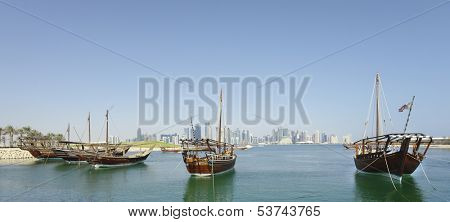 Dhows moored off Museum Park in central Doha, Qatar, Arabia, with some of the buildings from the city's commercial port in the background.