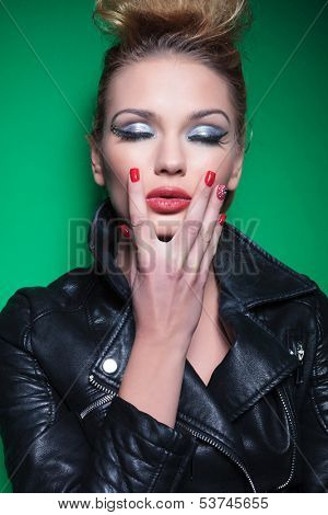 young beauty woman in leather jacket and beautiful make up touching her chin and keeps her eyes closed