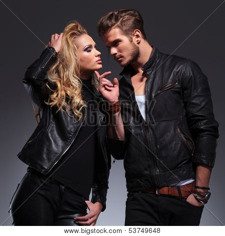 man holding his finger on his lover's chin and looks at her on gray background