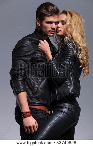 woman pulling her man closer to her while he looks away on gray background