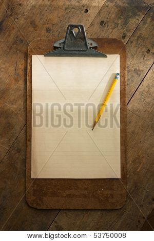 An vintage clipboard on a old wooden desk, with regular white blank paper. intentionally shot with stronger lighting on the upper half, so the message (to be inserted), stands out.