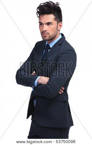 side view of a young business man with hands crossed looking away from the camera