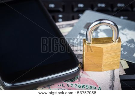 Locked padlock, phone, credit card and money on a black computer keyboard