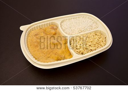 Frozen food: Chicken stroganoff with rice and shoestring potatoes package on brown leather background.