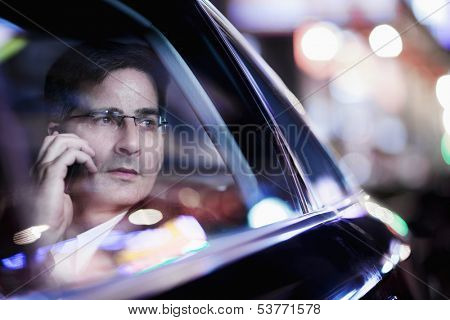 Businessman on the phone and looking out car window at night