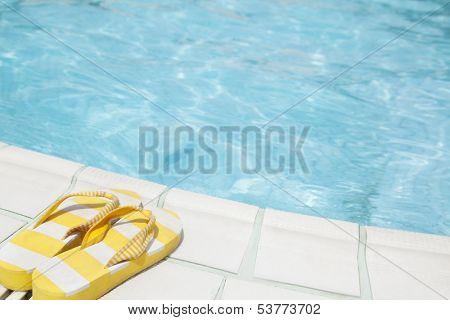 Pair of yellow flip flops by pool side