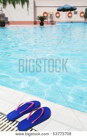 Pair of blue flip flops by pool side