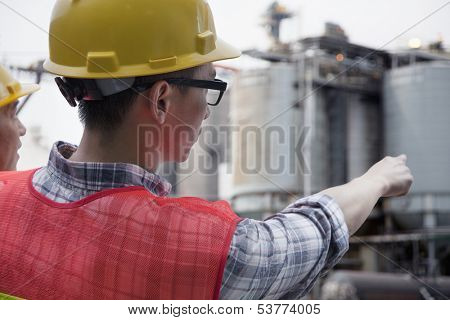 Two engineers in protective workwear pointing outside of factory