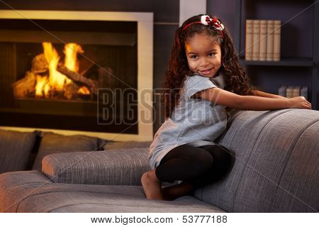 Beautiful afro little girl squatting on sofa in living room, smiling impishly.