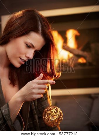 Beautiful young woman holding christmas bulb in front of fireplace.