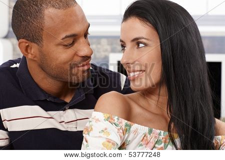 Loving mixed race couple looking at each other just about to kiss, smiling.
