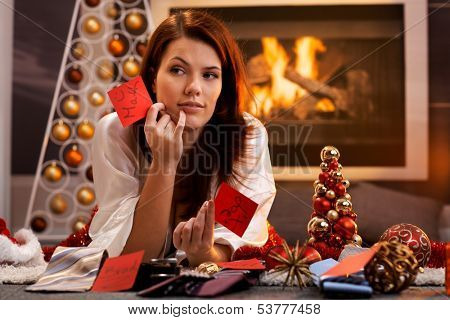 Woman arranging christmas gifts by fireplace, holding gift tag with male names, thinking, smiling, looking aside.