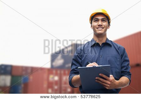 Smiling young engineer in protective work wear in shipping yard examining cargo