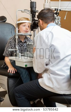 Male optician examining boy's eyes with slit lamp while sitting in store