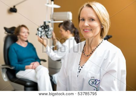 Portrait of confident eye doctor with colleague examining patient in background