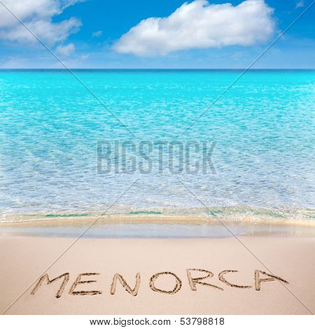 Menorca word written on sand of mediterranean beach with turquoise waters