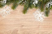 Christmas fir tree covered with snow on wooden board background