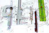 Micrometer Caliper Mechanical Pencil Compass and template ruler on Blueprint
