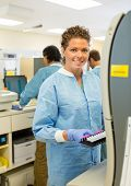 Portrait of happy female medical lab tech with sample for coagulation analysis poster