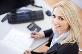 stock photo of calculator  - Beautiful businesswoman doing finances in the office - JPG