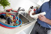 stock photo of clog  - Hands of professional Plumber with a wrench - JPG