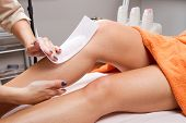 stock photo of pulling hair  - Beautician waxing a woman - JPG
