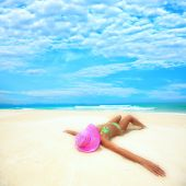 image of sunbathing woman  - Woman in pink hat lies on the beach - JPG