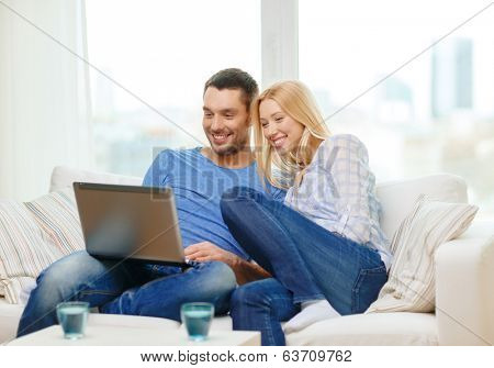 love, family, technology, internet and happiness concept - smiling happy couple witl laptop computer at home