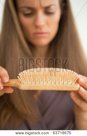 Closeup On Concerned Young Woman Looking On Hair Comb