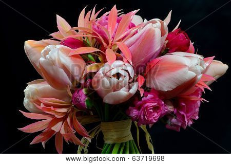 A Posey Os Tulips And Pieris Against A Black Background