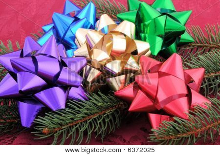 Assorted Bows Laid On A Evergreen Branch
