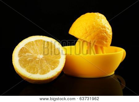 Citrus squeezer with lemons on black background