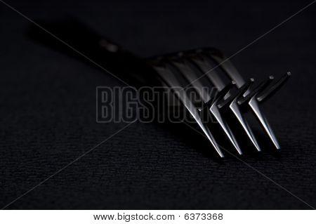 Two forks on black background
