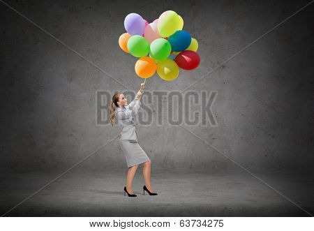 business and education concept - smiling businesswoman pulling down bunch of balloons