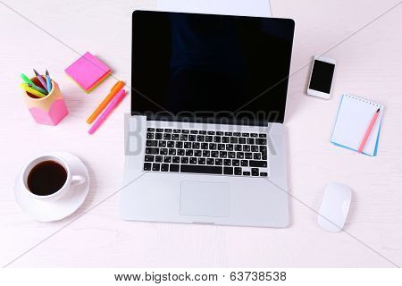 Office workplace with open laptop on wooden desk