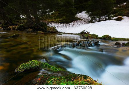 flowing water of river over mossy stones in clean nature landscape