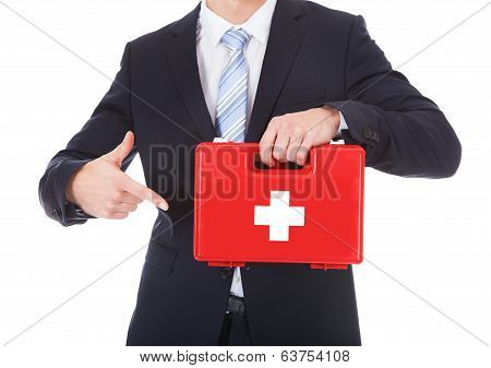 Businessman Pointing At First Aid Box